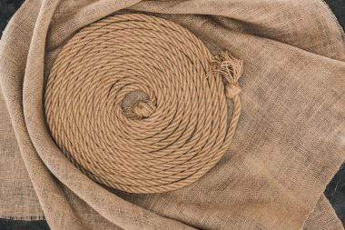 top view of brown nautical rope arranged in circle on sackcloth on dark concrete surface