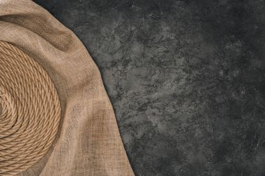 top view of brown nautical rope arranged in circle on sackcloth on dark concrete tabletop