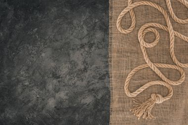 top view of arranged brown nautical rope on sackcloth on dark concrete tabletop