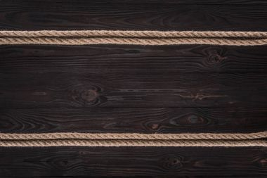 Top view of arrangement of brown nautical ropes on dark wooden tabletop stock vector