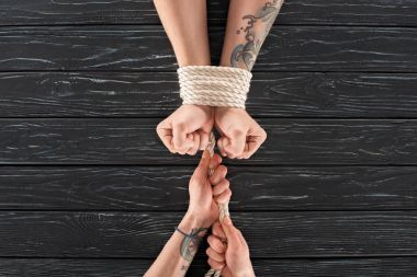partial view of woman tying rope around males hands on dark wooden surface