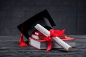 Stacked books with diploma and graduation hat on table