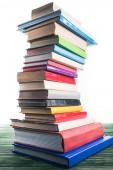 hoher gebogener Turm aus gestapelten Büchern auf Holztisch