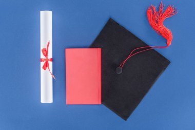 Graduation cap with diploma and book isolated on blue