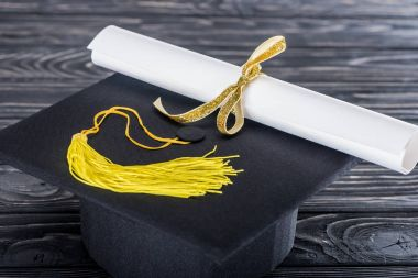 Graduation hat and diploma with yellow ribbon on wooden table