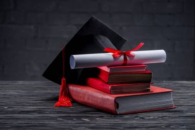 Stack of books with diploma and graduation hat on table