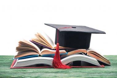 Graduation cap on stack of open books stock vector