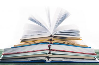 Stack of open books on wooden table