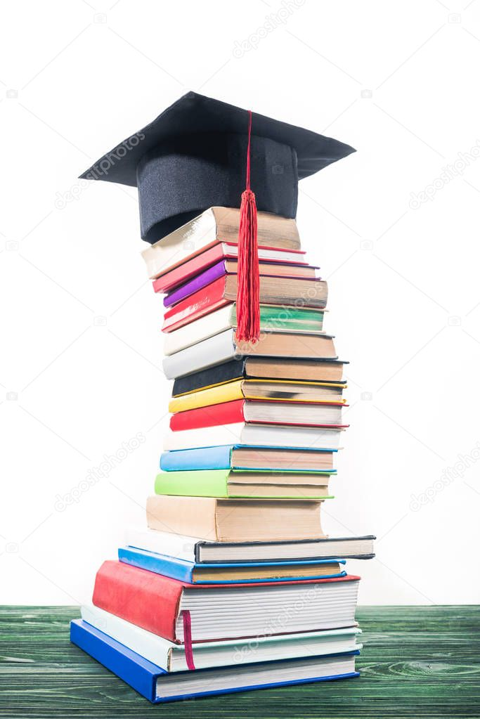 Graduation cap on bent tower of stacked books stock vector