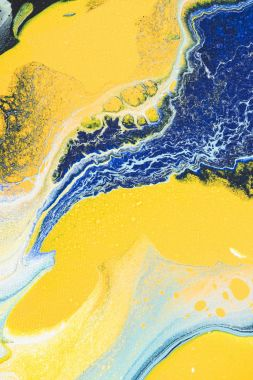 close up of abstract texture with yellow and blue acrylic paint