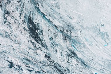 Close up of light blue and white brush strokes of oil paint