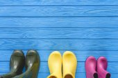 Photo top view of colorful rubber boots placed in row on blue wooden planks