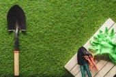 pohled shora zahradnické nářadí a ochranné rukavice na trávě