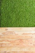 Photo top view of green lawn and wooden planks background