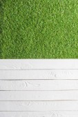 Fotografie top view of green lawn and white wooden planks background