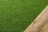 Fotografie top view of green lawn and wooden plank background