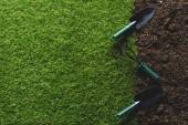 pohled shora trávy a lopaty s ruční hrábě na půdě