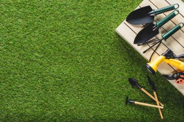 top view of gardening tools and equipment on grass