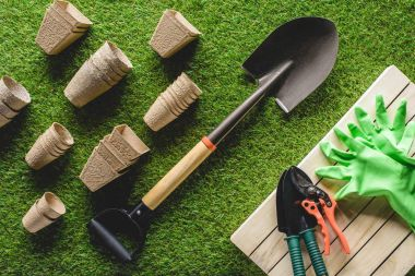 top view of arranged flower pots and gardening equipment on grass