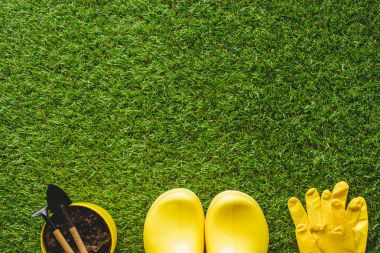 top view of yellow rubber boots, protective gloves and flower pot with gardening tools