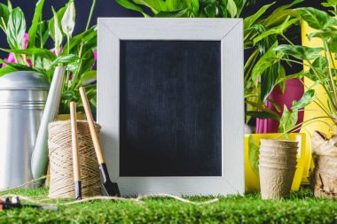closeup shot of empty blackboard and gardening equipment on lawn