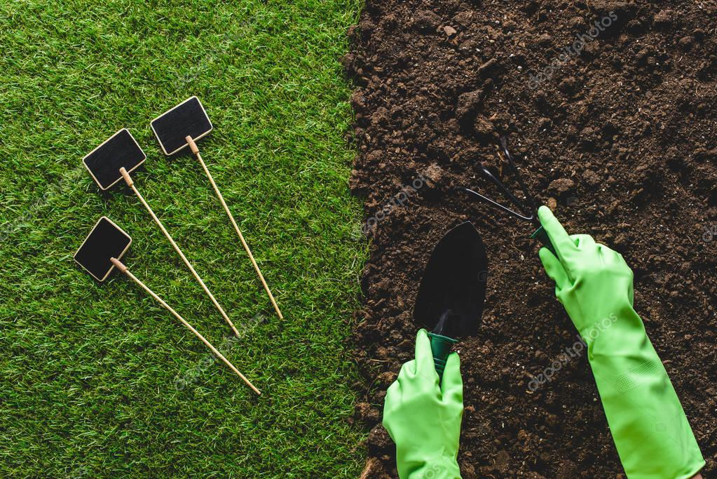 Cropped image of gardener in protective gloves working with gardening tools and empty blackboards on grass