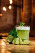 Fotografie Nahansicht des grünen Van Gogh cocktail im Glas mit Minze und Limette auf Holztisch