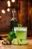 Fotografie Nahansicht des grünen Van Gogh cocktail im Glas mit Flasche Absinth auf Holztisch