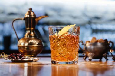 close-up view of glass with old fashioned cocktail on table