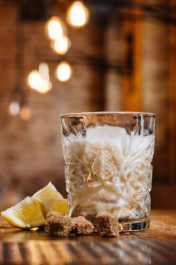 close-up view of glass with cream alcohol cocktail, lemon and brown sugar on wooden table