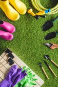 top view of empty blackboards, rubber boots, protective gloves and gardening equipment on grass