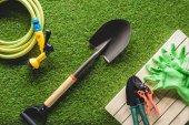 pohled shora na hadici, ochranné rukavice a zahrádkářských potřeb na trávě