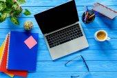Nyitott laptop és levélpapír kék fa tábla