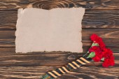 Photo top view of empty old paper and carnations wrapped by st. george ribbon
