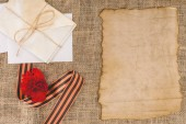 Photo top view of st. george ribbon, carnation, old empty paper, stack of letters