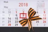 Detailní záběr kalendáře s datum ot 9. květen a luk od stuha st. george