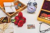 Fotografia primo piano ha sparato di sveglia, occhiali, fiori avvolti da nastro di St. george, lettere, medaglie su grigio, concetto di giorno di vittoria