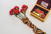 Photo closeup shot of flowers wrapped by st. george ribbon and box with medals, victory day concept