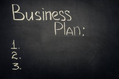 Business plan inscription with stages list on dark chalkboard