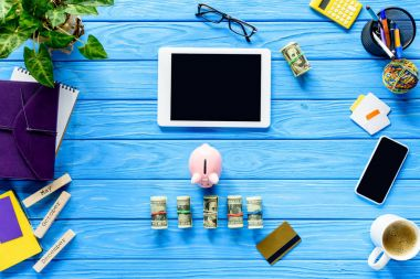 Digital tablet with piggy bank and money on blue wooden table