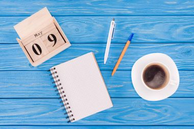 Top view of wooden calendar with date of 9th may, coffee cup, empty textbook and pens, victory day concept stock vector