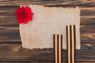 top view of old empty paper, carnation and st. george ribbons on wooden surface