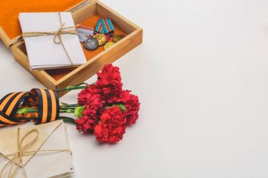 closeup shot of box with medals, stacks of letters, carnations wrapped by st. george ribbon on gray, victory day concept