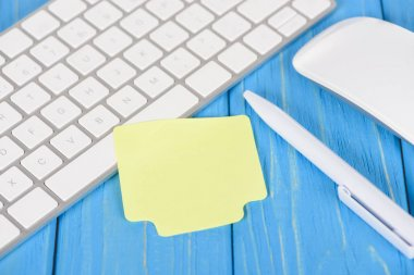 Closeup shot of empty note paper, pen, computer keyboard and mouse on blue wooden surface stock vector