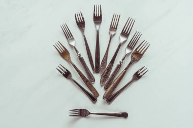 Composition of old metal forks on white background