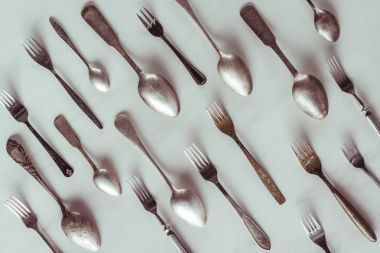 Vintage spoons and forks on white table