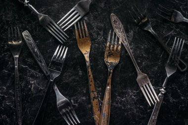 Old metal forks on rusted background