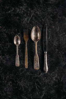Old rusted silverware set on dark marble table