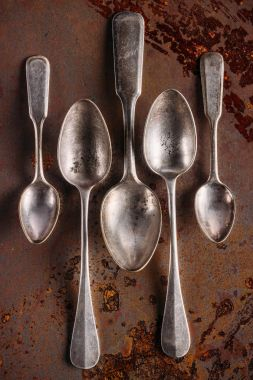 Set of old spoons on vintage rusted table