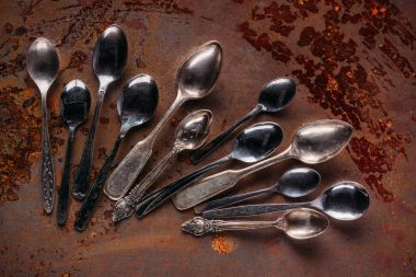 Various vintage spoons on rusted table
